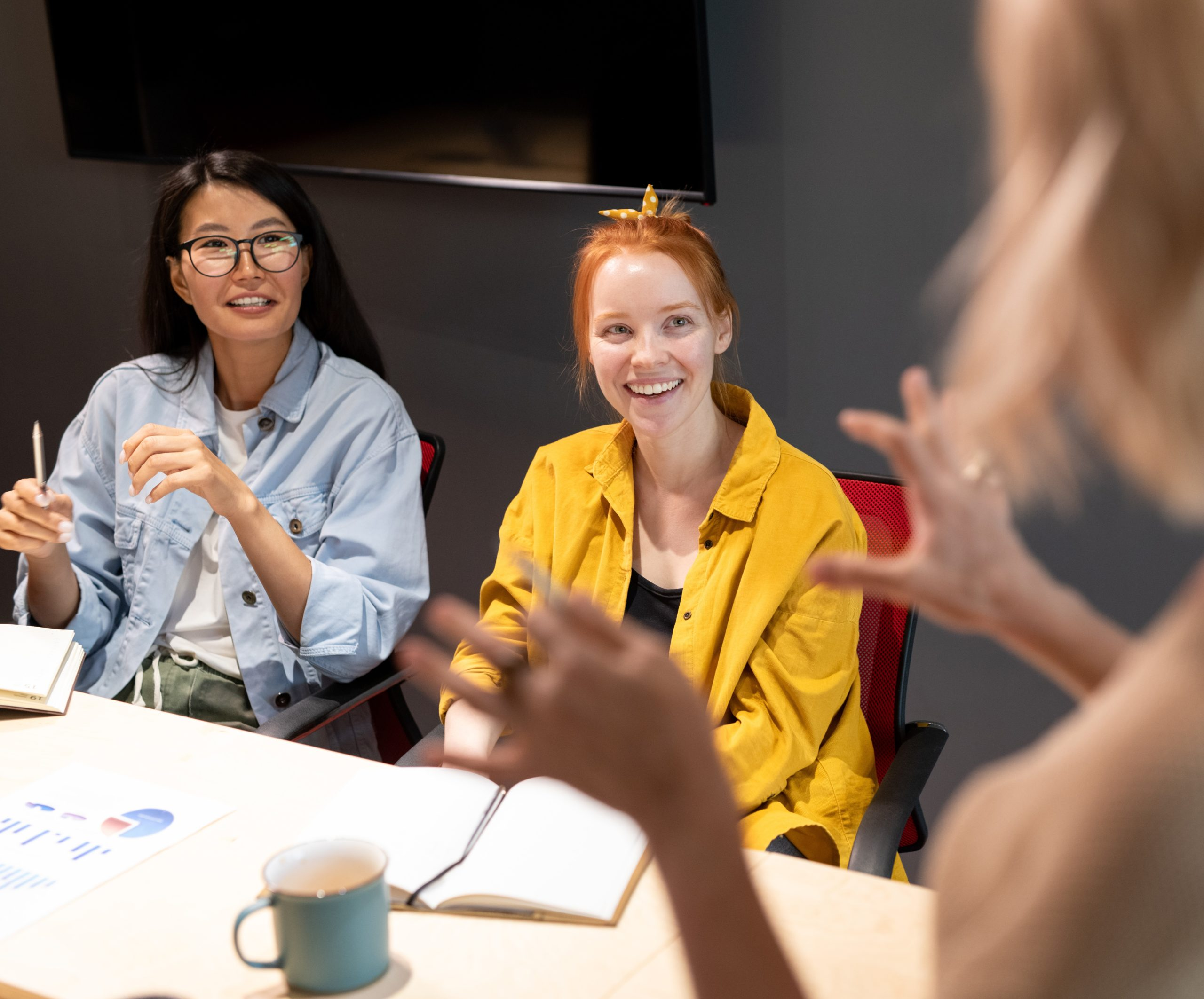 Happy young intercultural businesswomen in casualwear looking at business coach>